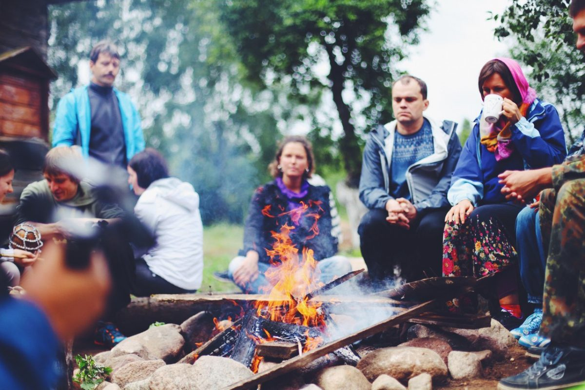 people relax in open air by the fire